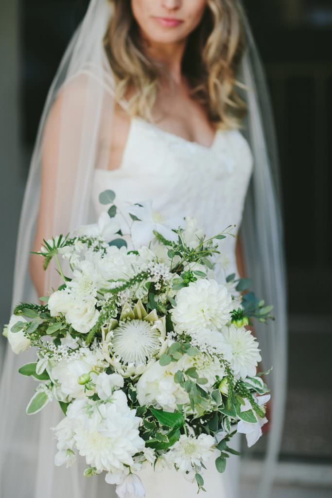 a green and white bridal bouquet with a white protea on maui