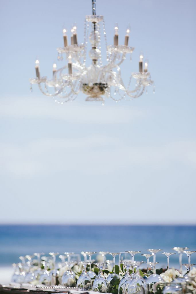 a chandelier hangs above glassware and flowers on a table with the ocean in the background