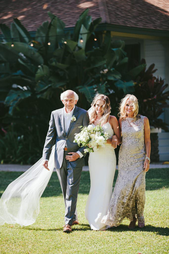a bride is escorted down the aisle by her parents at olowalu plantation house maui
