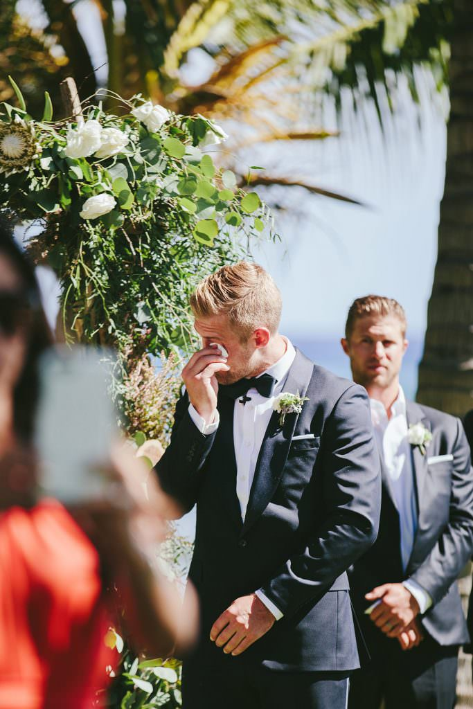 a groom wipes a tear from his eye at his maui wedding ceremony
