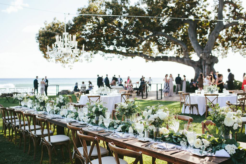 long wooden tables with white florals and chandelier at olowalu plantation house maui