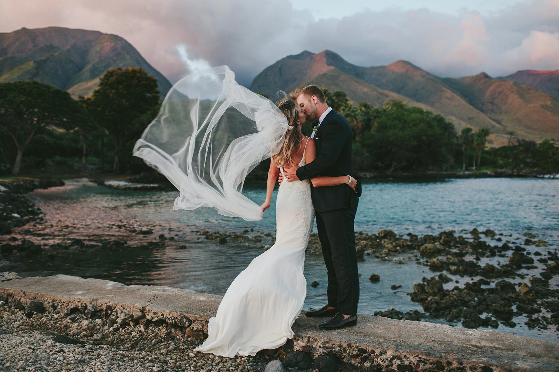 bride and groom kiss in front of the west maui mountains with veil blowing in the wind