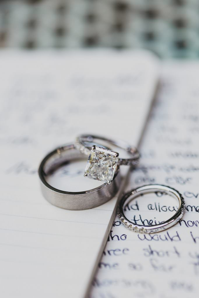 platinum wedding bands and a square cut diamond engagement ring sit atop hand-written vows