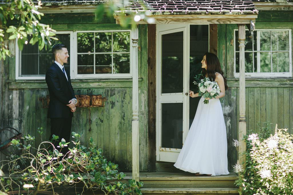 a bride and groom greet each other on the veranda of a cane house in Maui