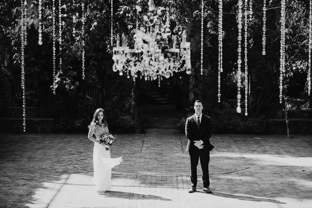 a bride and groom stand beneath a chandelier at the Haiku Mill on Maui
