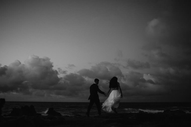 a bride and groom walk at dusk on Maui's windy north shore