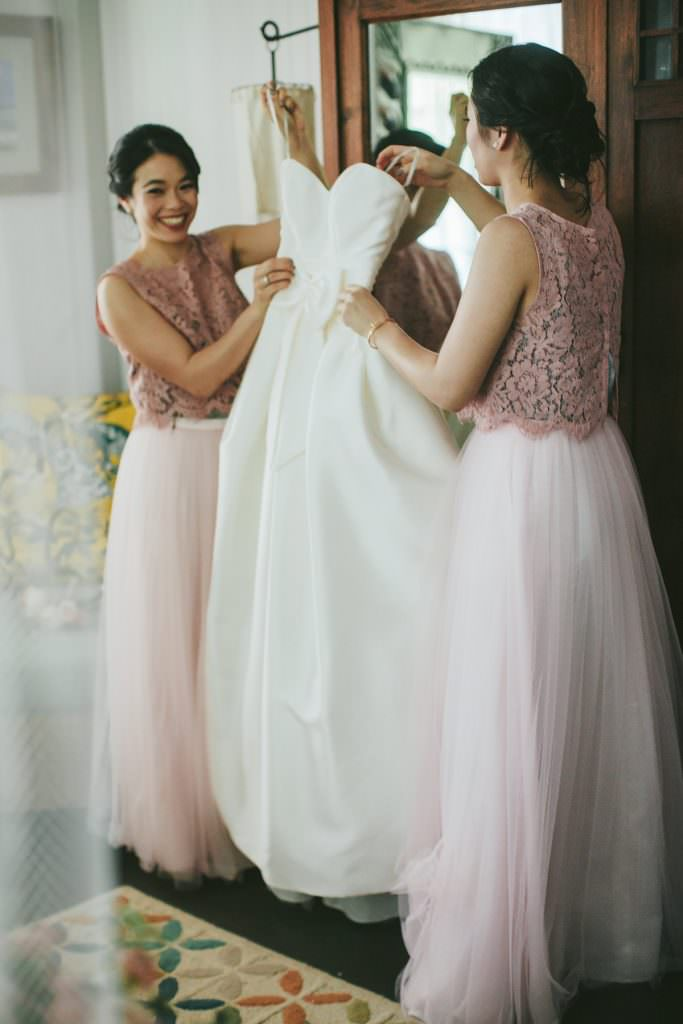 bridesmaids assist with a wedding dress in maui