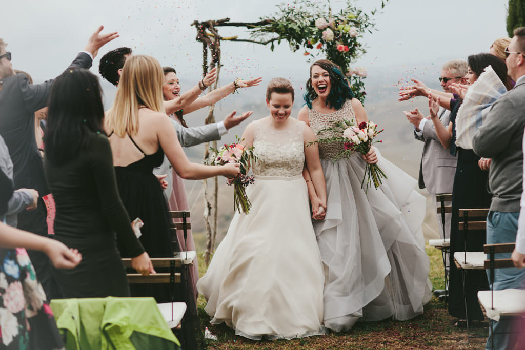 two brides just married walking down the aisle through multi colored confetti