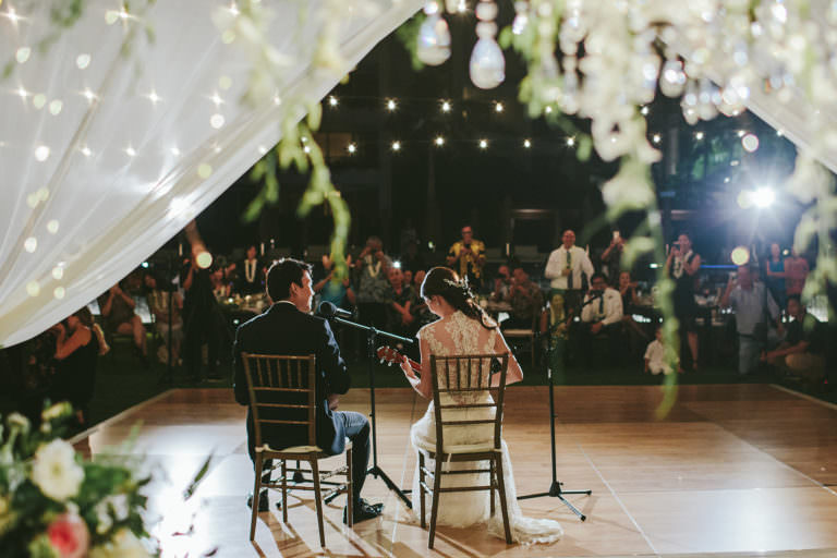 a bride and groom serenade their guests with ukulele at their hawaii wedding reception