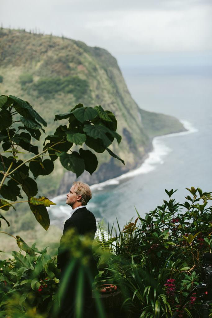 a groom waits for his bride overlooking Waipio Valley on the big island of Hawaii
