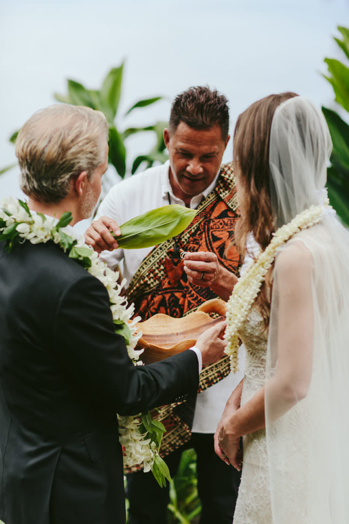 a Hawaiian wedding officiant uses a ti leaf to bless the wedding rings with water on the island of Hawaii