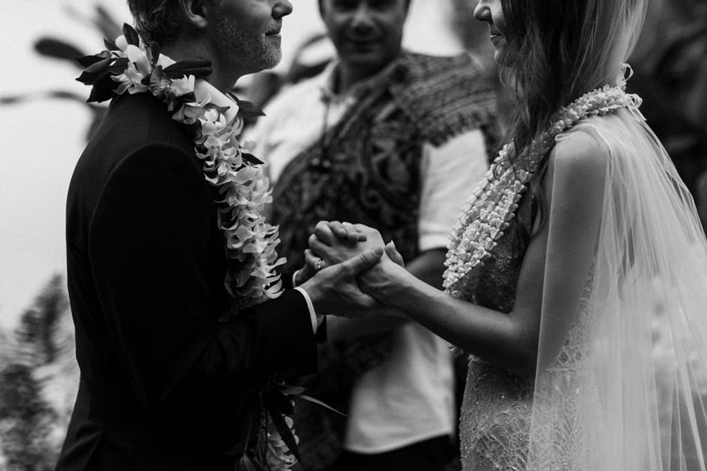 a bride and groom clasp hands exchanging wedding vows on the island of Hawaii