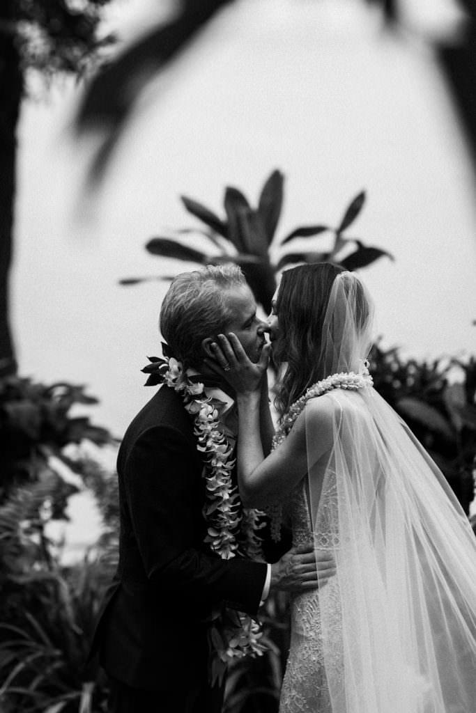 a bide and groom kiss after their Hawaiian wedding ceremony