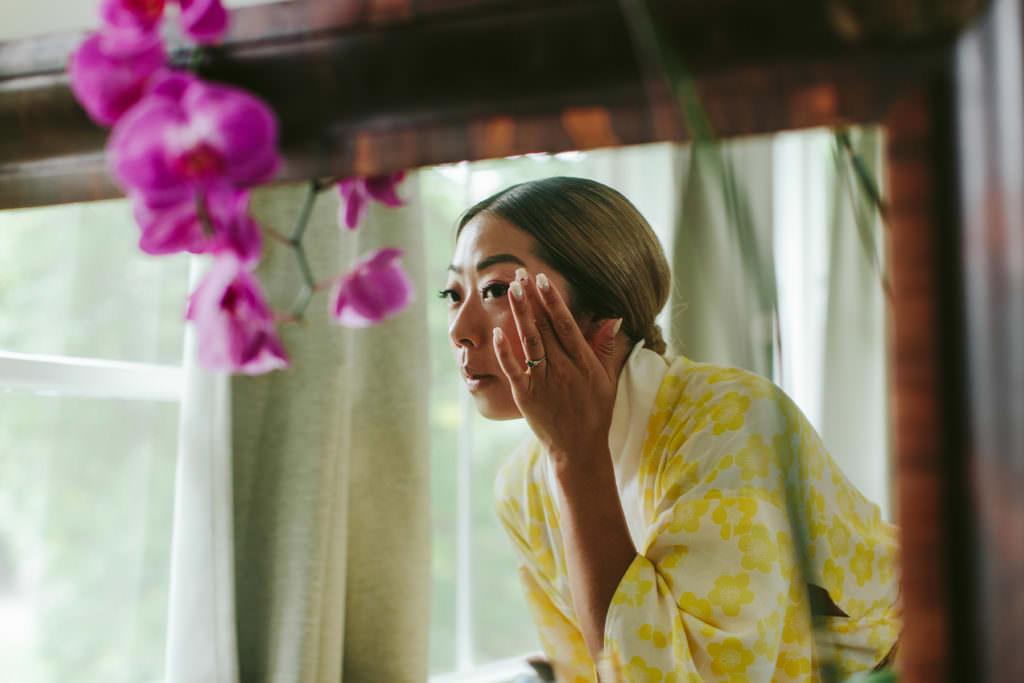 a bride in a yellow kimono applies makeup in a mirror