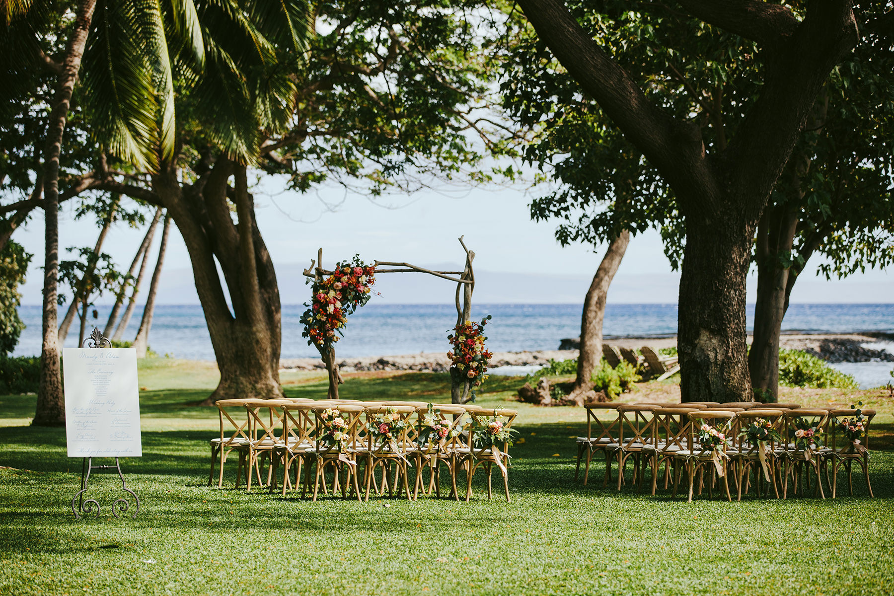 a driftwood floral arch and rustic chairs set by the ocean for a wedding ceremony at Olowalu Plantation house on Maui