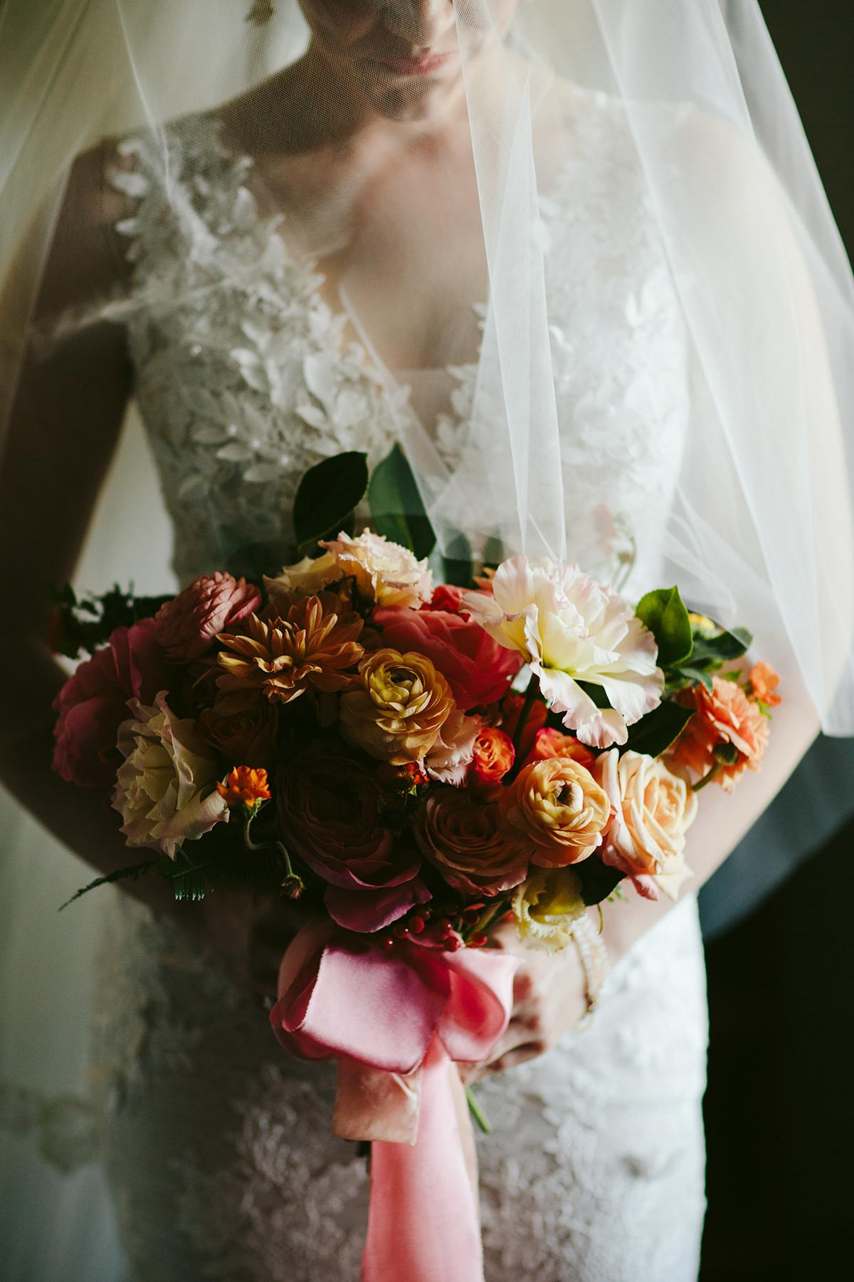 a citrus hued bridal bouquet with orange ribbon held by a Maui bride