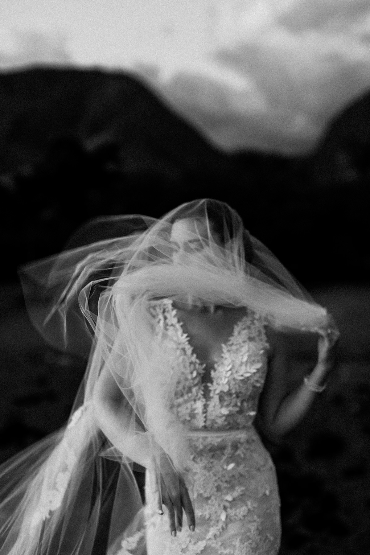 black and white photo of a veiled Maui bride in a Mira Zwillinger gown in the wind