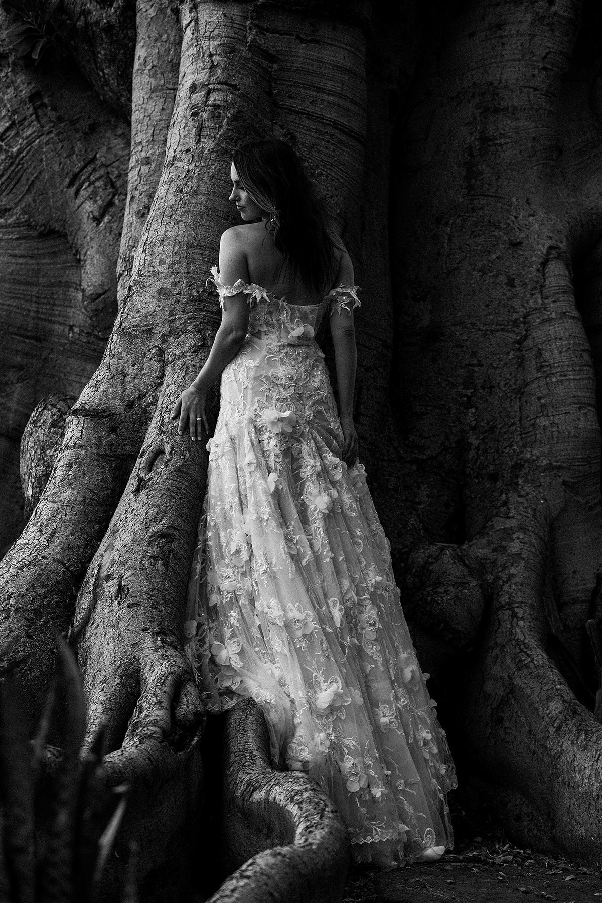 a bride in a Galia Lahav gown poses in a large tree at Olowalu Plantation House