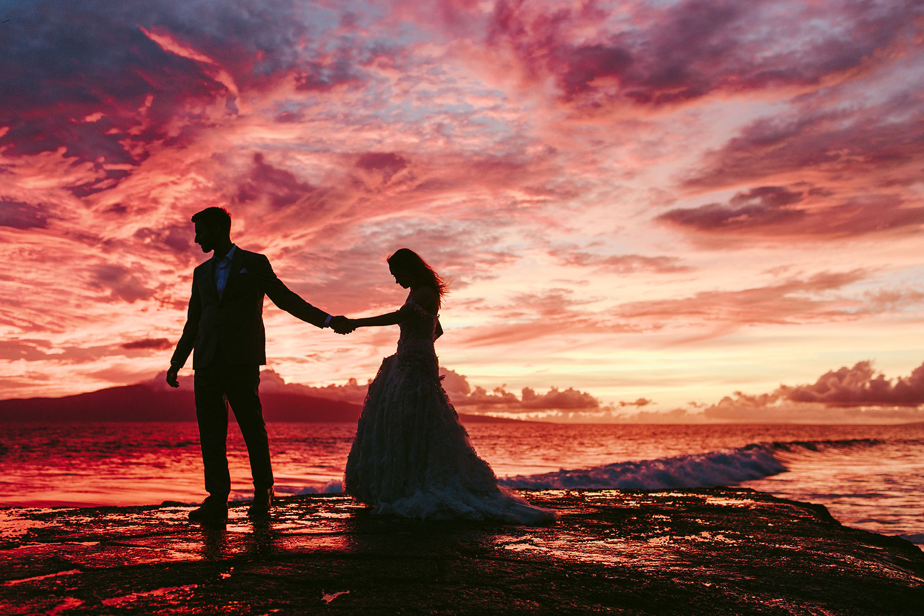 a bride and groom silhouetted against a vibrant sunset at Olowalu Plantation House Maui
