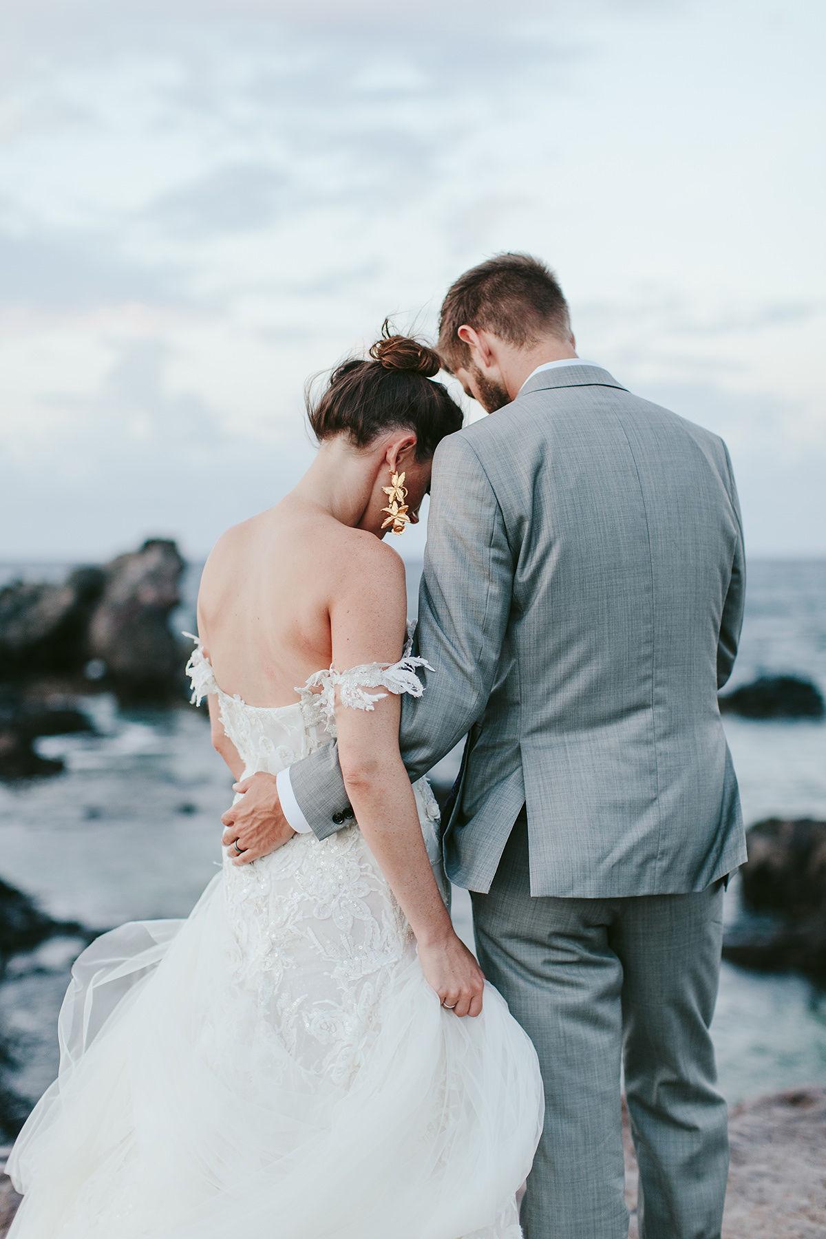 the backs of a bride and groom near the Maui ocean