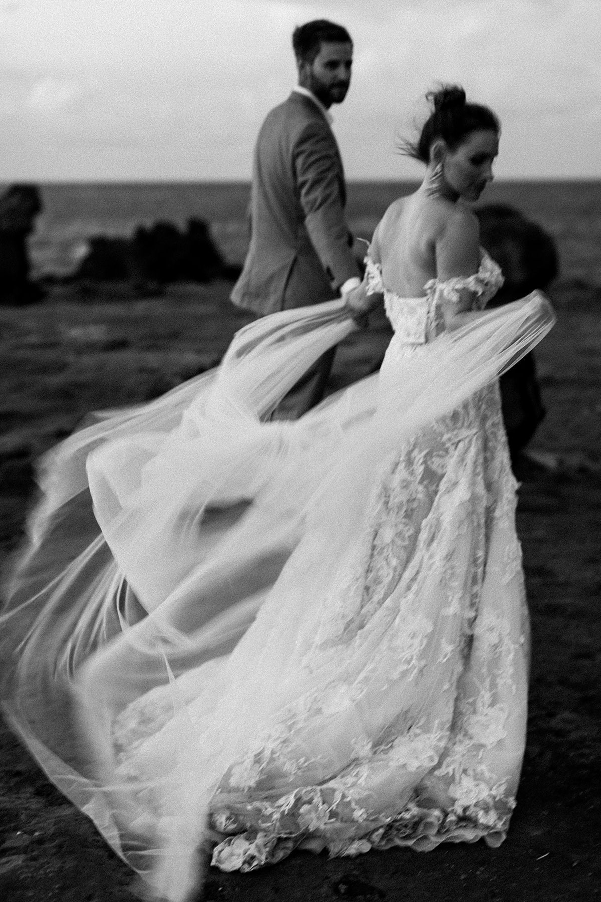 a bride's veil blows in the wind by the ocean on Maui's north shore