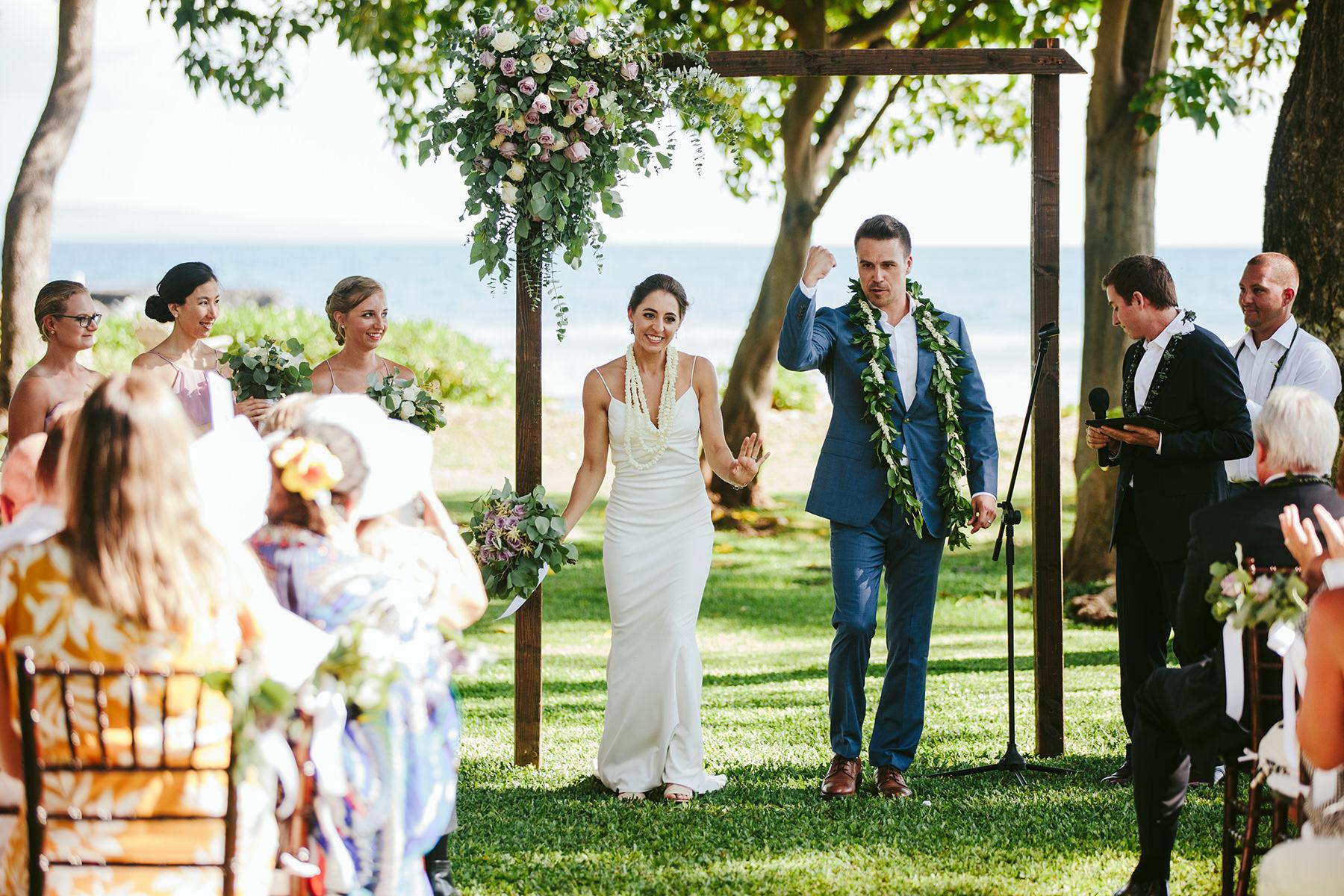 a bride and groom celebrate under their wedding arch at Olowalu Plantation House Maui