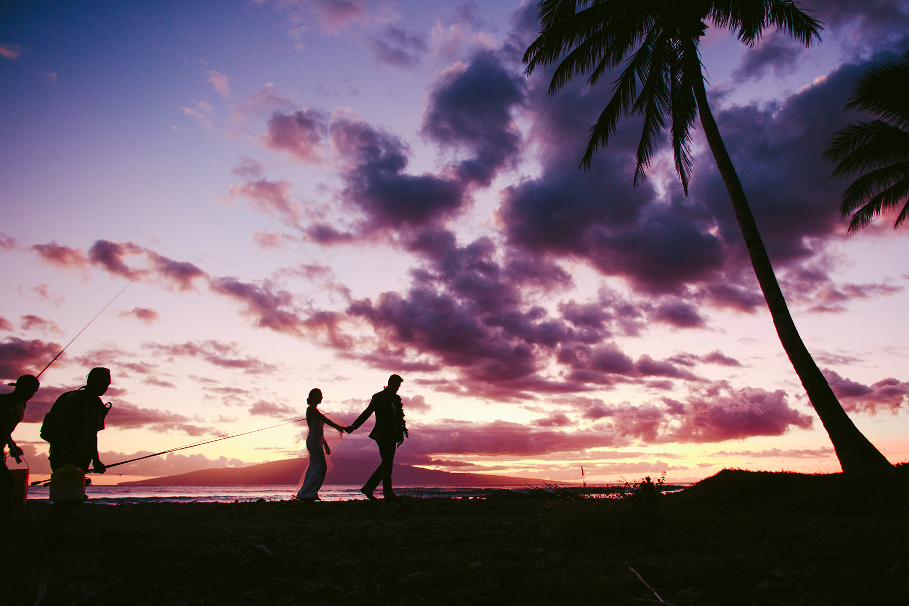 a bride and groom in silhouette against the sunset at Olowalu Plantation House